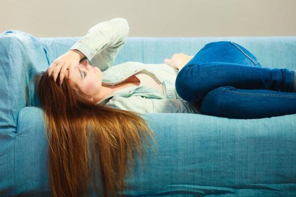 頭痛でソファに横たわる女性
