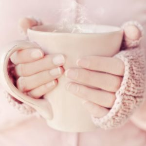 温かい飲み物の入ったカップを持つ女性の手元