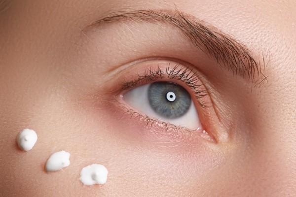 保湿クリームを塗る女性の目元アップ