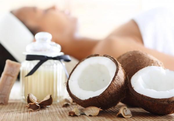 ココナッツの実とココナッツオイル、マッサージを受ける女性
