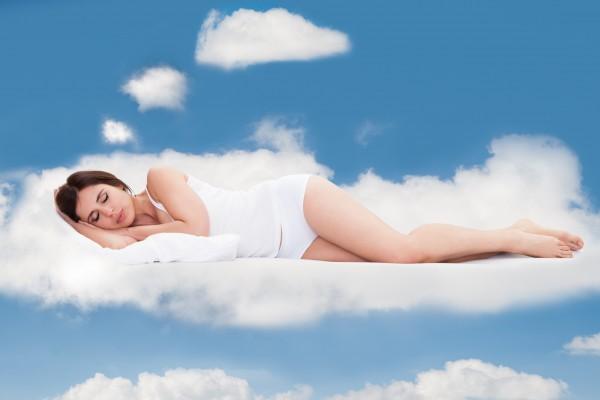 雲の上で気持よく眠る女性