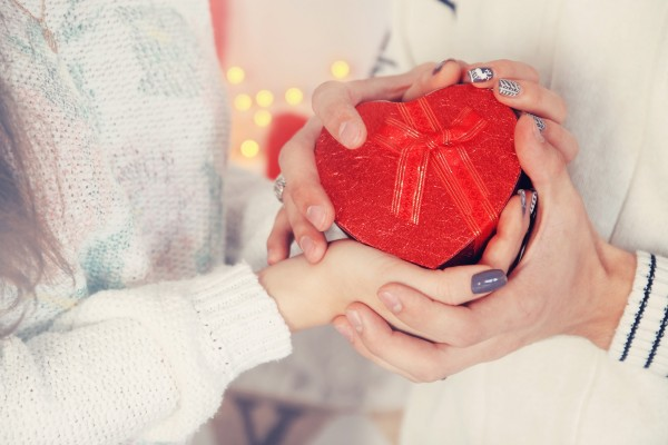 ハート型のプレゼントを持つ男女の手