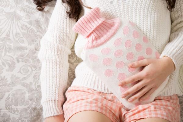 湯たんぽで腹部を温める女性