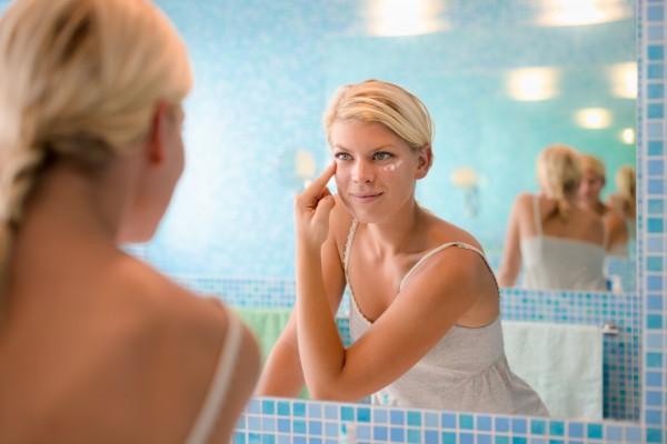 顔にクリームを塗って保湿する女性