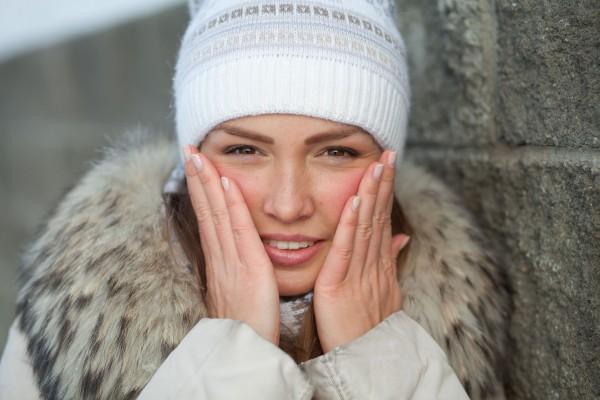 寒さで赤い顔を押さえる女性