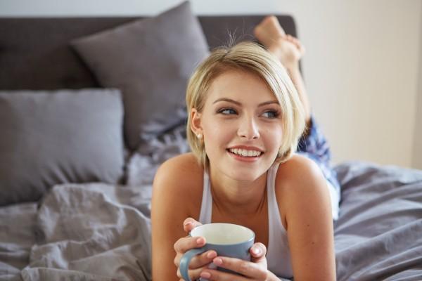 ベッドでお白湯を飲む女性