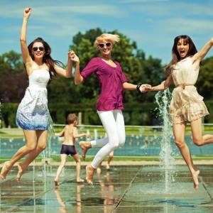 噴水の前でジャンプする3人の女性