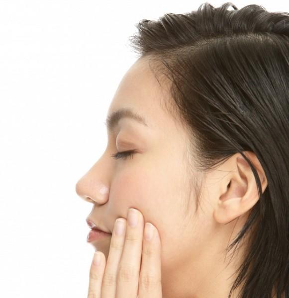 顔のツボ押しをする女性