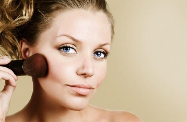 頬骨にチークを塗る女性
