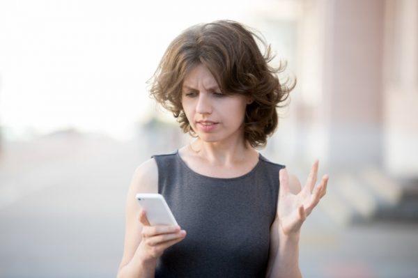 朝に携帯を見て不快な顔をする女性