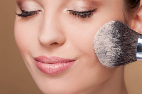 ルースパウダーを顔に塗る女性