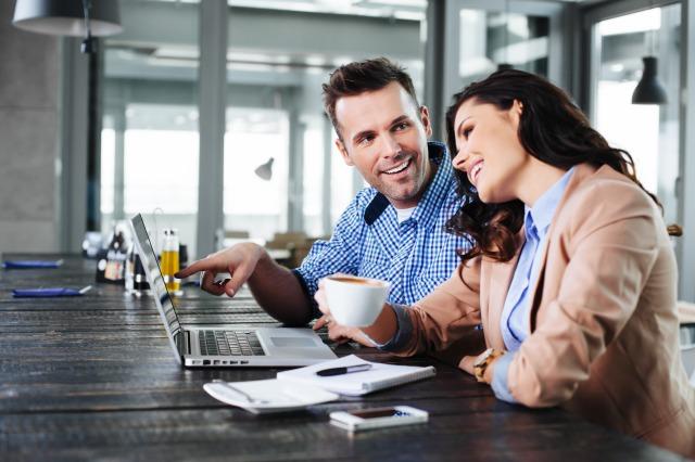パソコンを見ながら話す男女