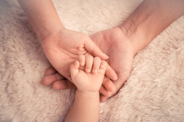 赤ちゃんと両親の手