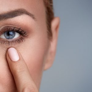 目の下のまぶたを引っ張る女性